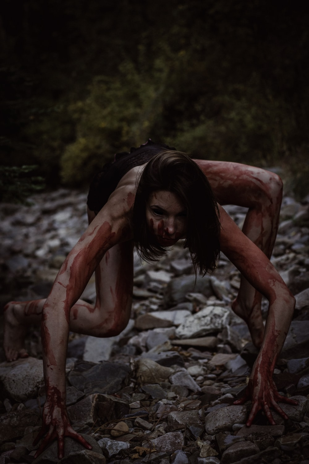 crawling woman covered with blood on stones