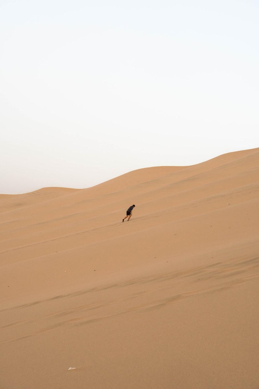 man climbing sand dunes