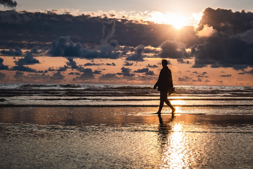 silhouette photography of person walking by the seashore during golden hour