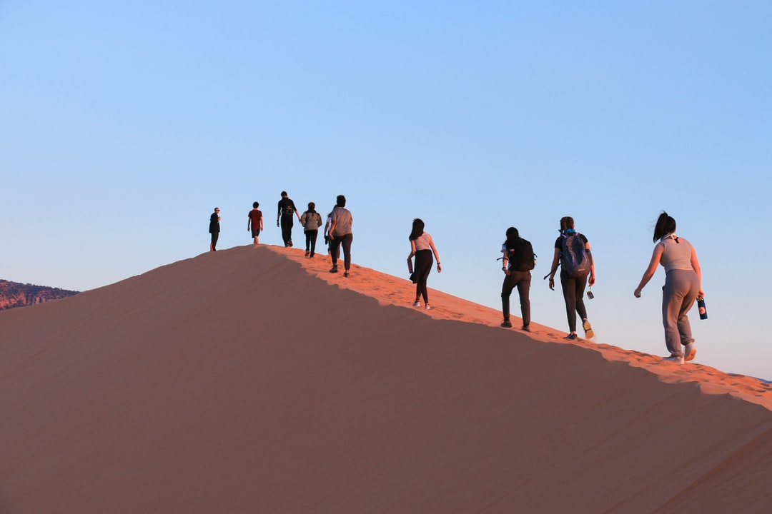 Teenagers trekking to the top of a sand dune