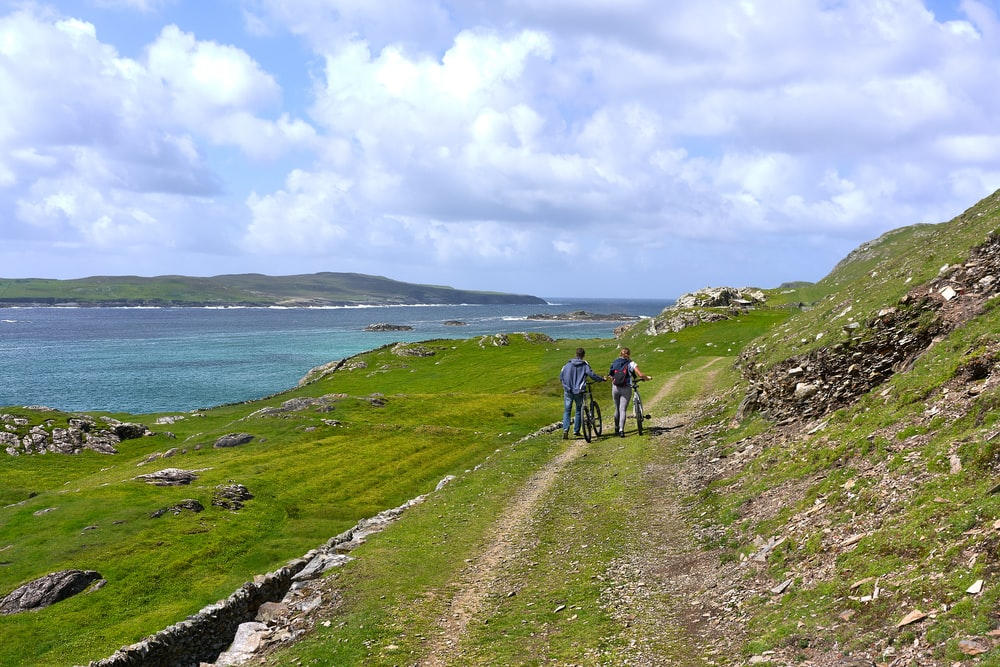 two people walking together with bikes in green field viewing mountain and blue sea under white and blue sky during daytime