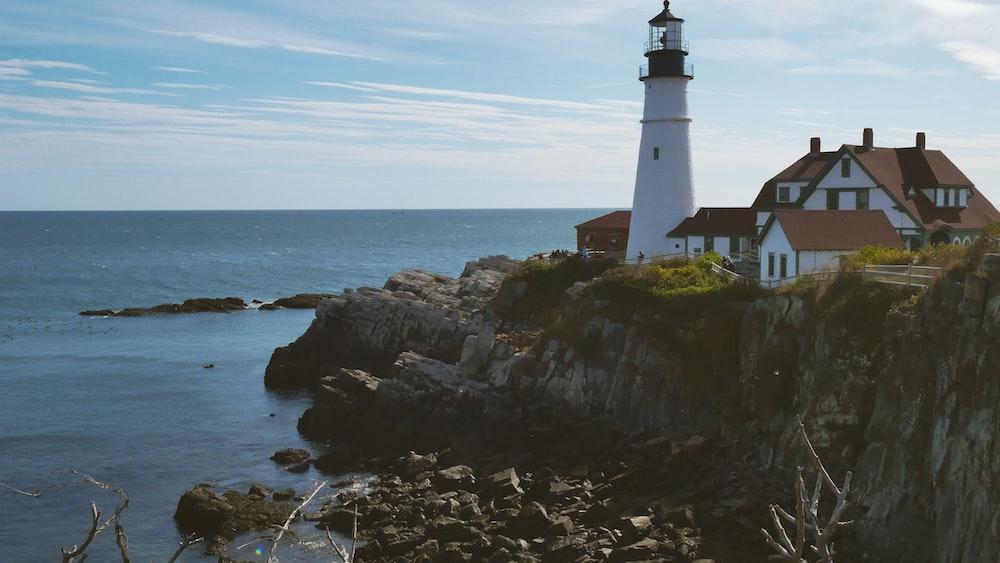 lighthouse on hill facing ocean