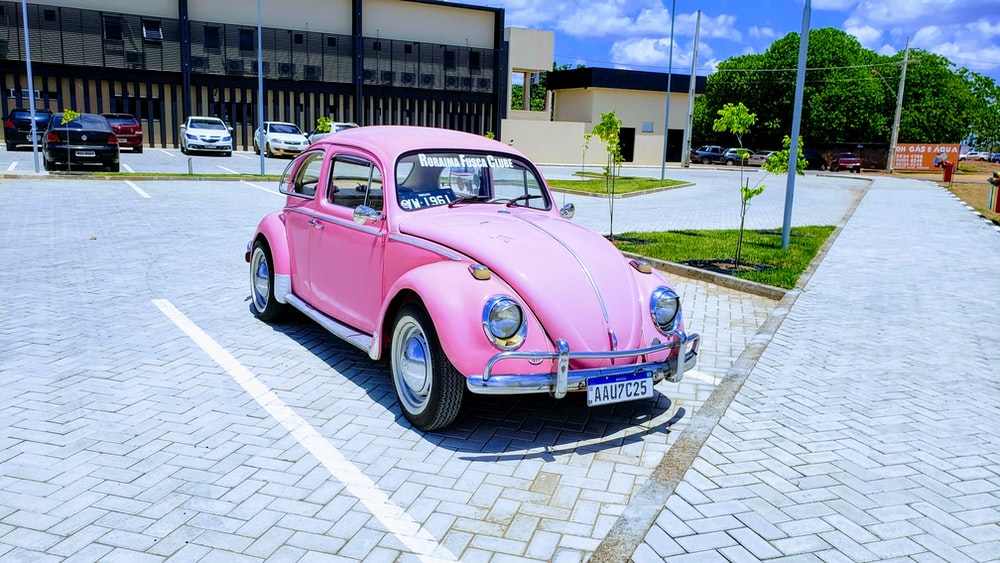 pink Volkswagen Beetle coupe parking near road during daytime