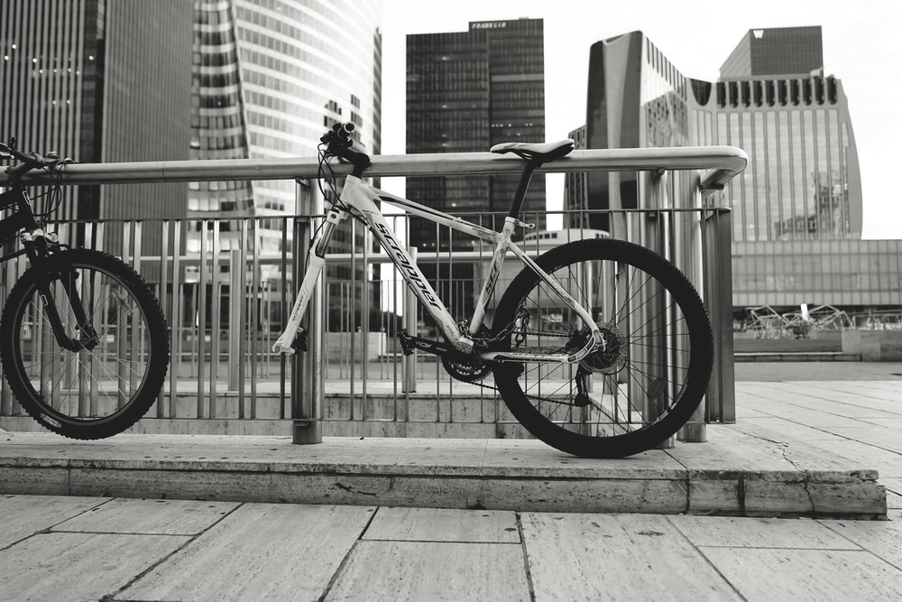 grayscale photography of a bicycle parked on sidewalk