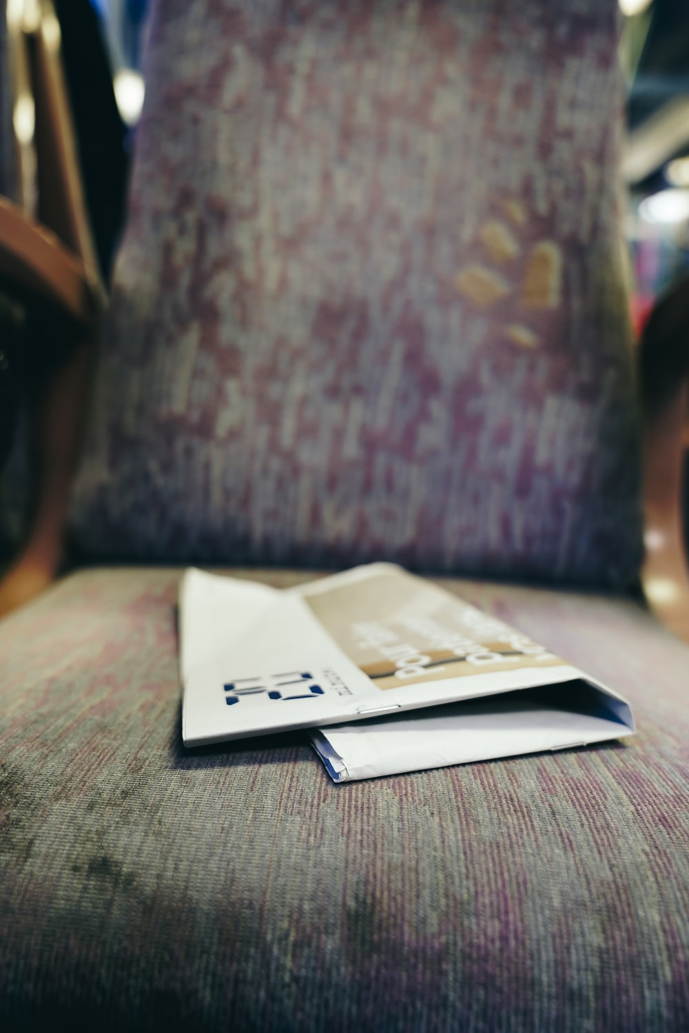 white and brown paper flyer on a fabric padded sofa chair