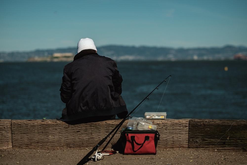 man sitting beside black rod