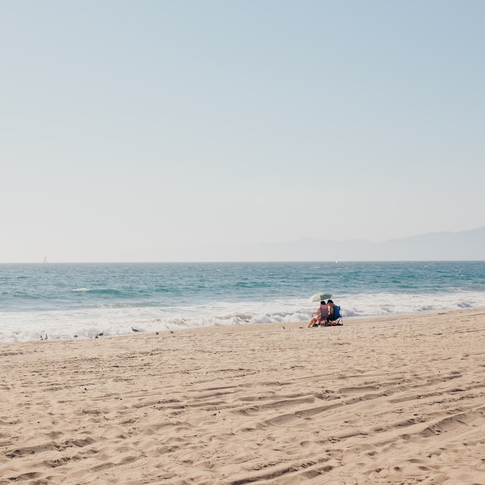 two person sitting on shore at daytime