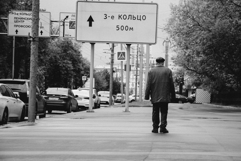 grayscale photography of man walking on sidewalk beside roadsign