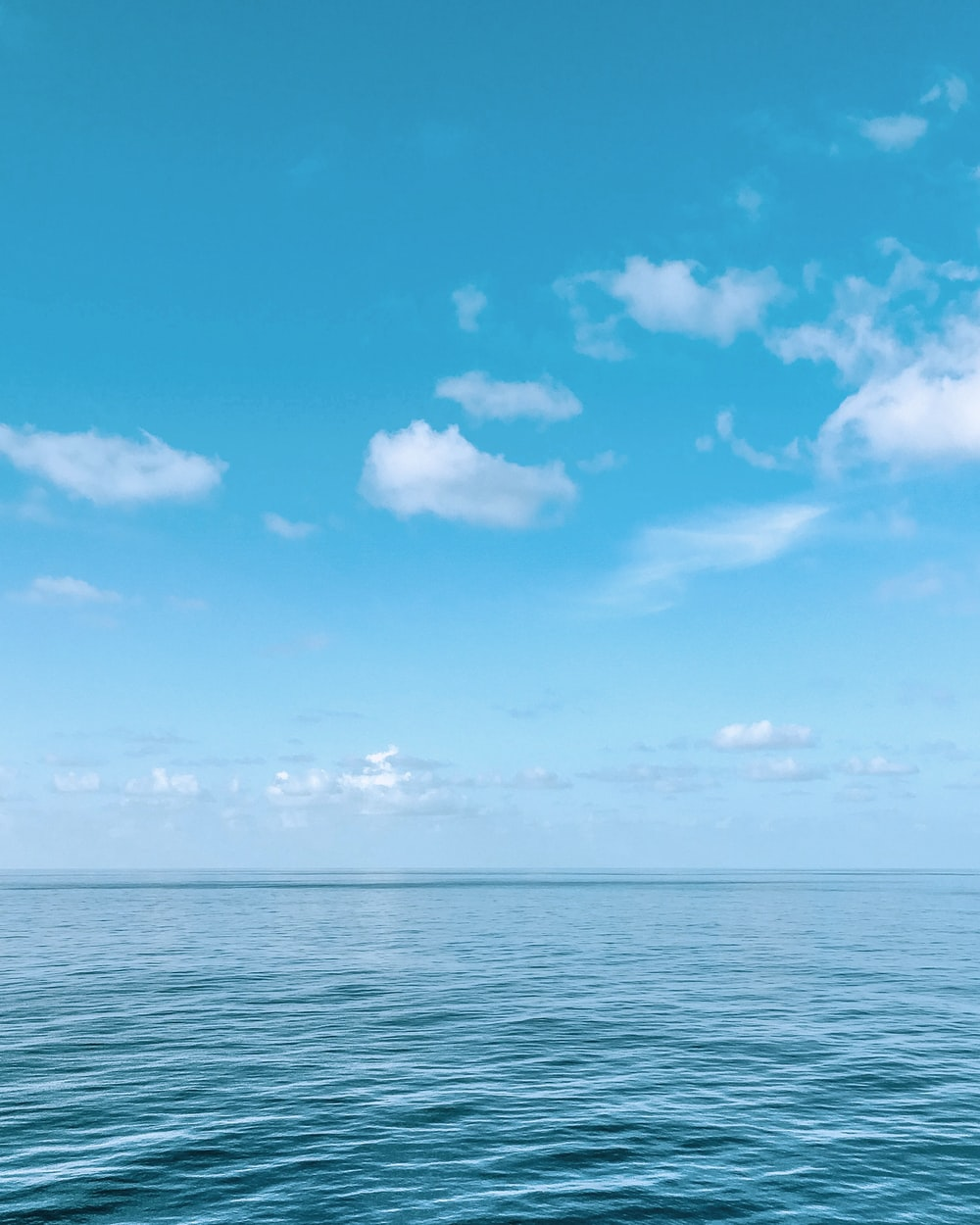 blue body of water under blue and white sky during daytime
