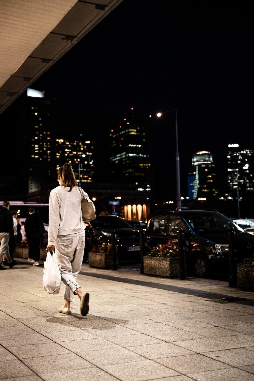 woman wearing white long-sleeved shirt holding plastic bag walking on pathway during night time