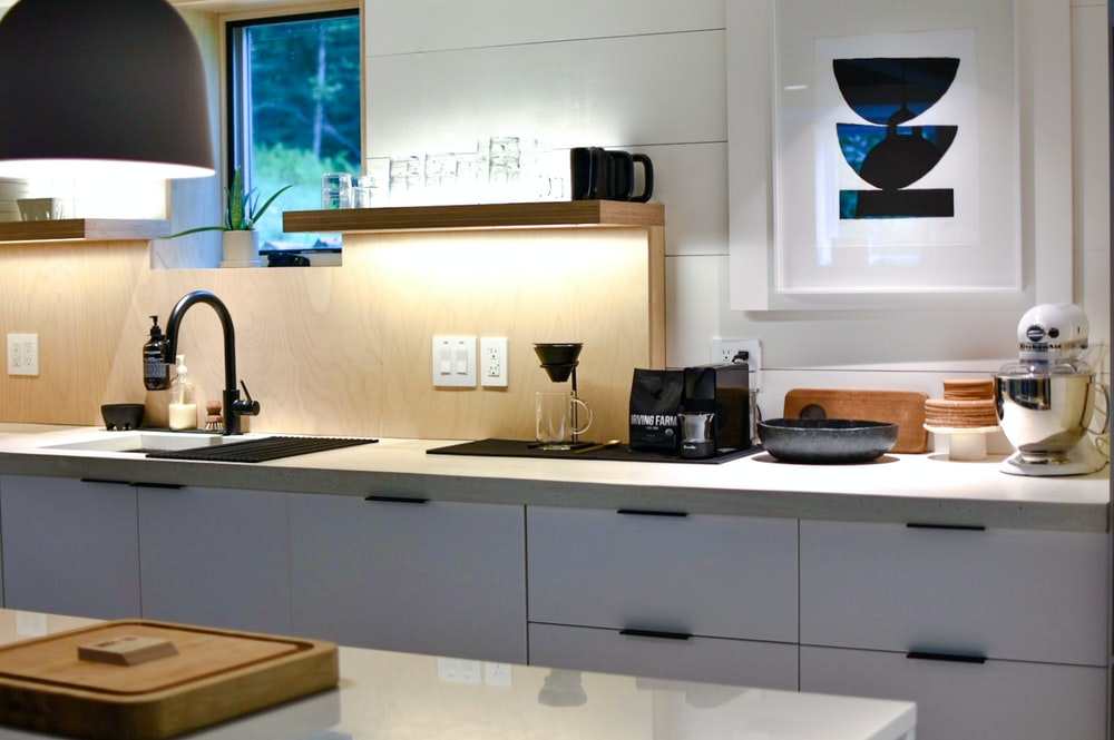 white stand mixer and coffee maker near sink