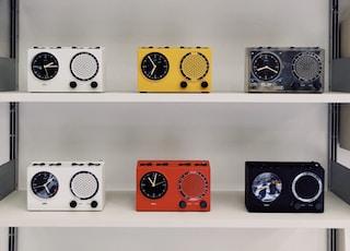 assorted-color portable alarm clocks displayed on a rack