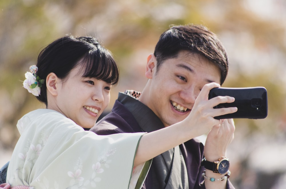 selective focus photography of man and woman taking selfie near outdoor during daytime