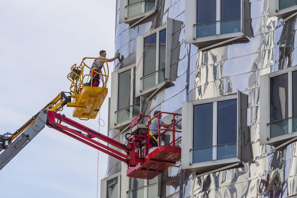 man wearing gray t-shirt working on building