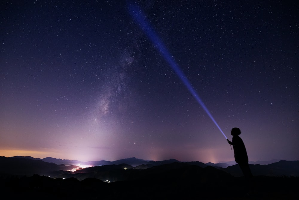 man standing on peak while holding flash light at night