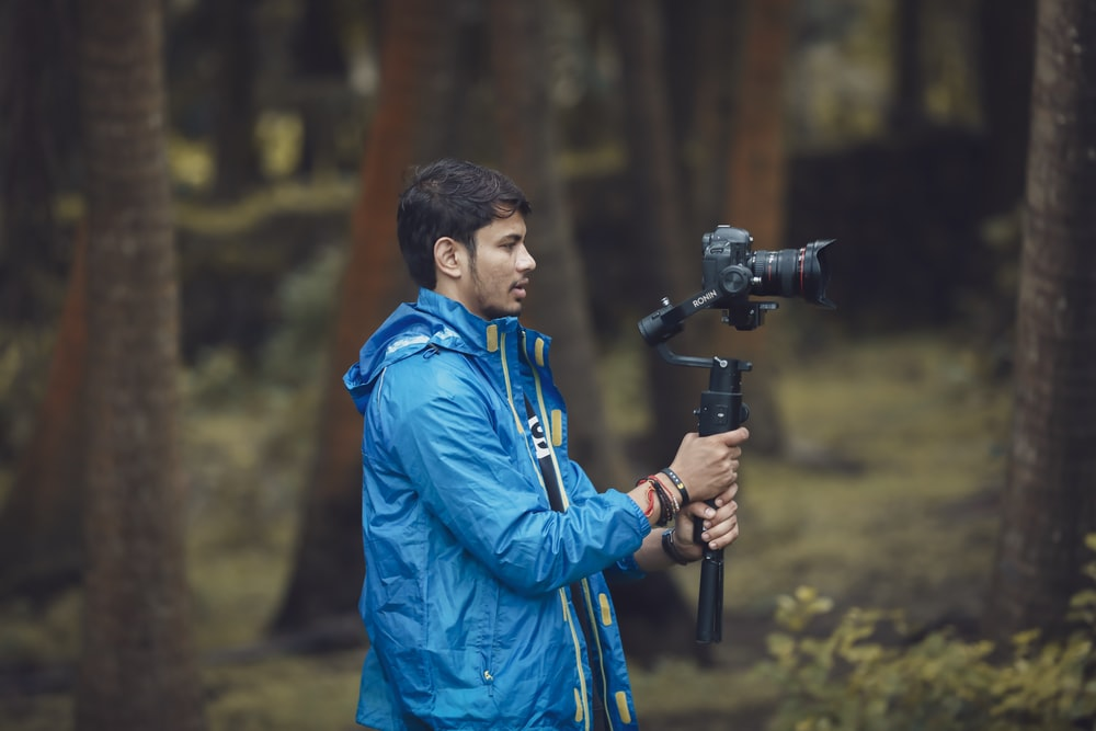 man wearing blue jacket holding tripod with DSLR