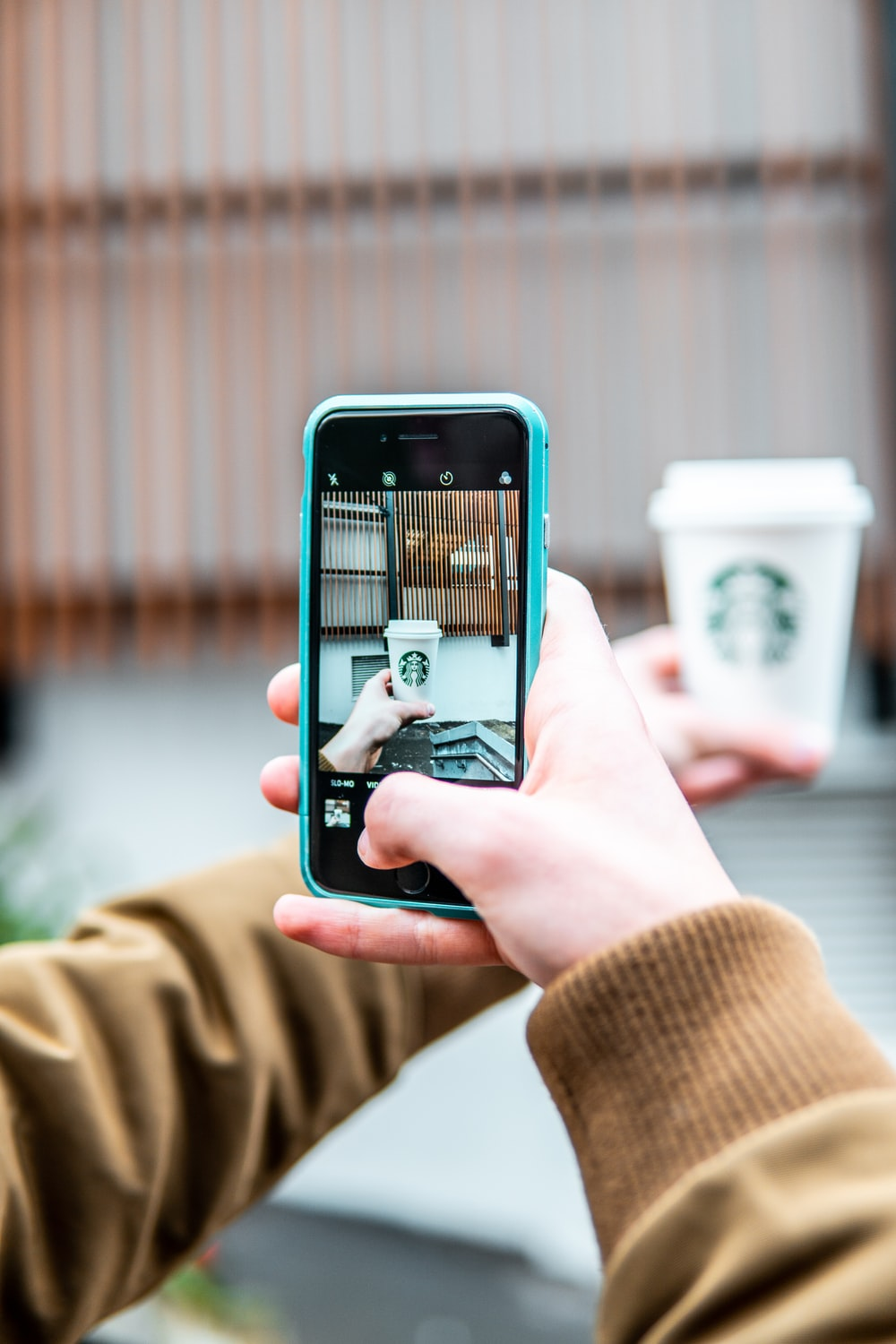 person taking photo of Starbucks cup
