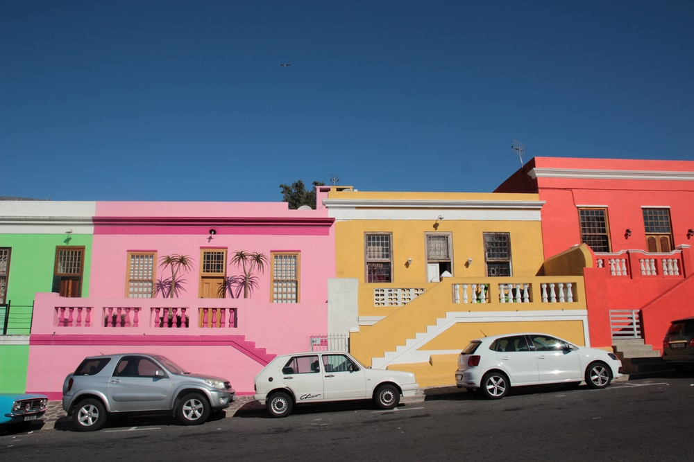 parked cars near multi-colored house