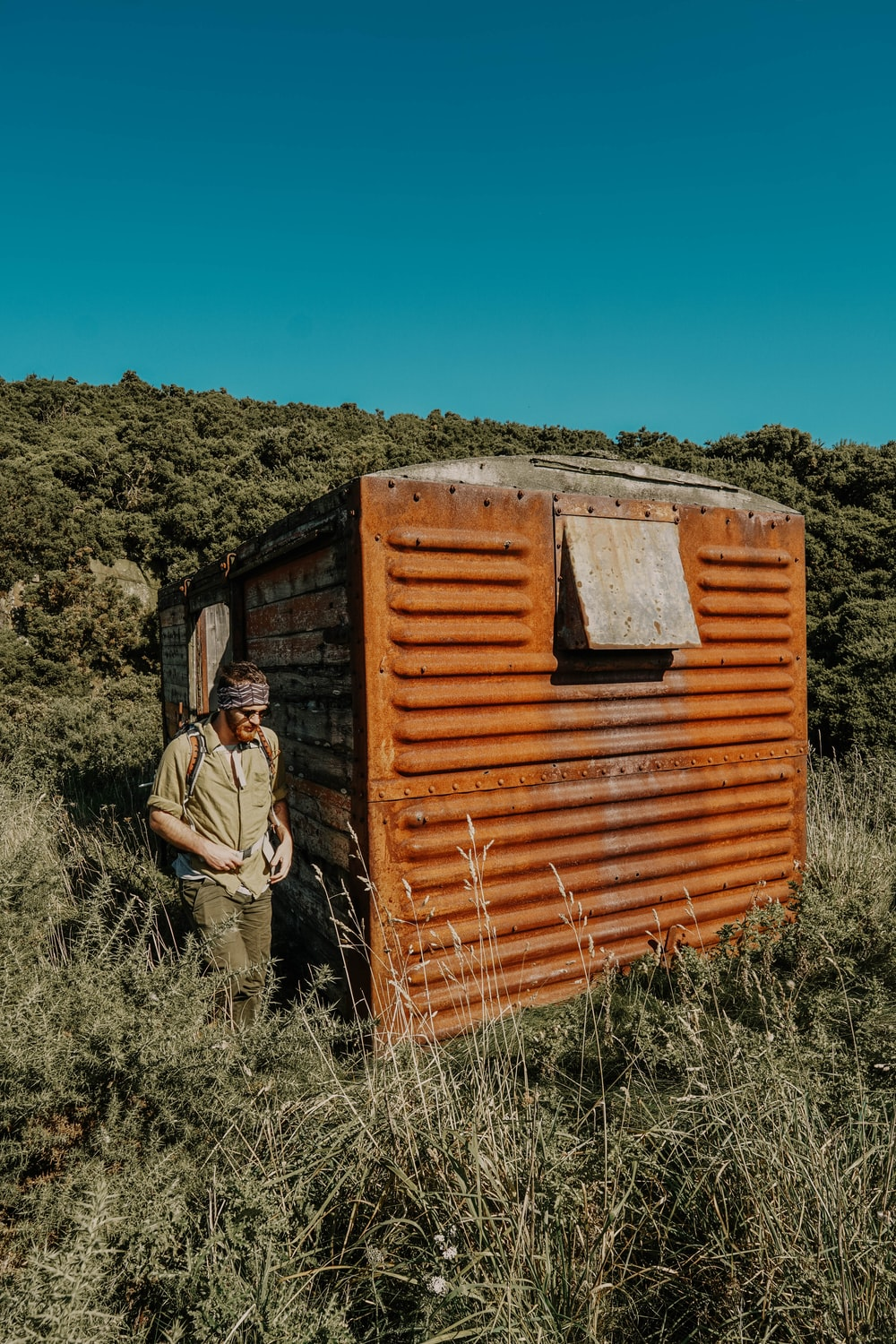 man standing beside shed on grass field during day