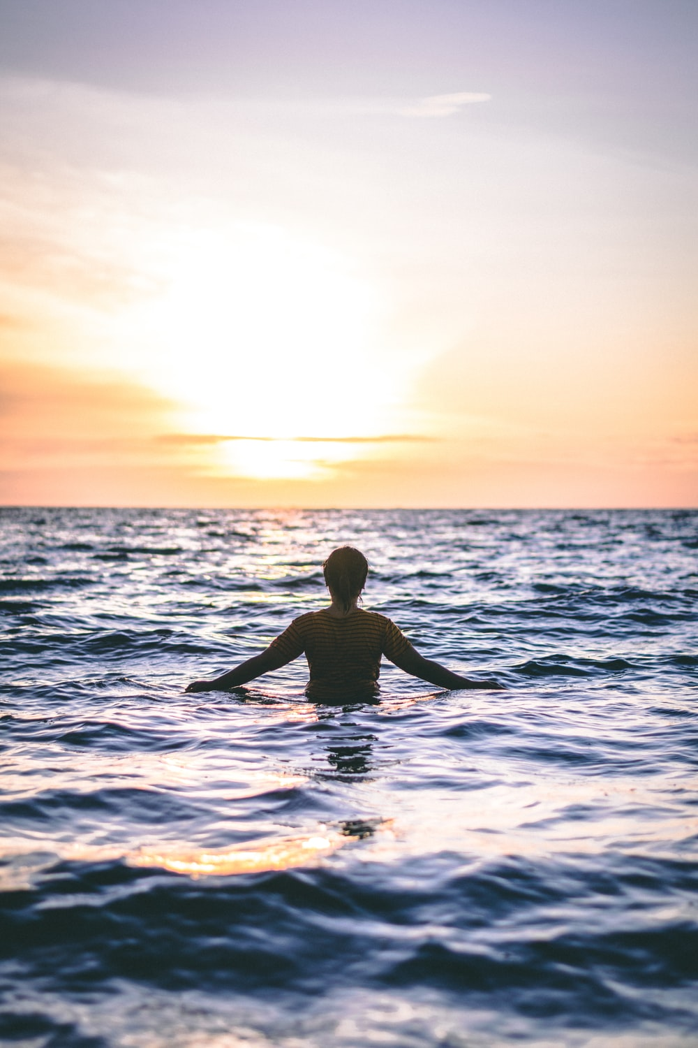man in the ocean during day