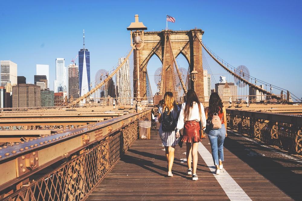 three woman walking on bridge