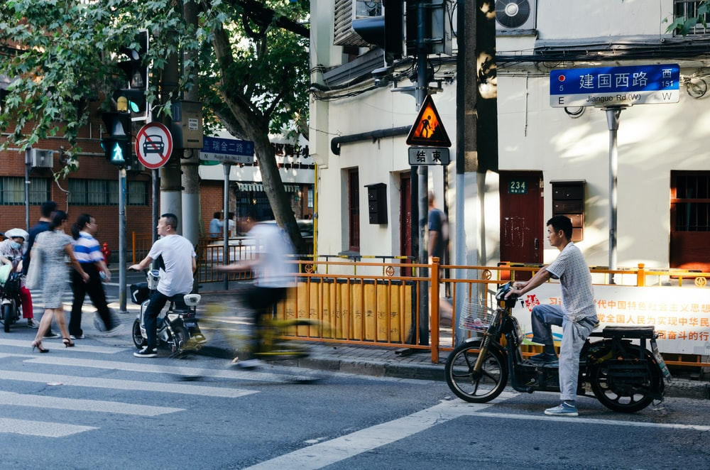 people walking and riding bikes and motorcycles near building during day