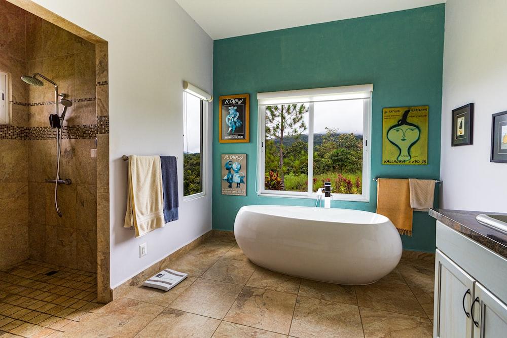 white bathtub beside window