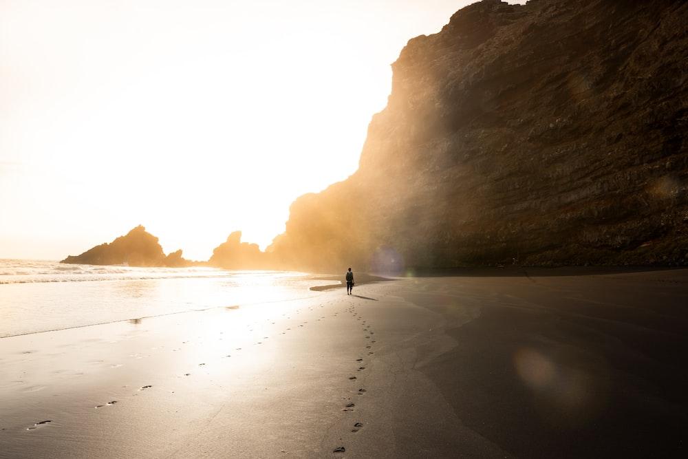 man on shore near rock formation