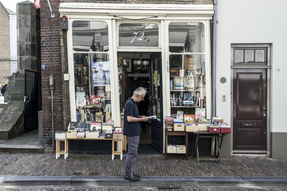 man standing in front of a bookshop