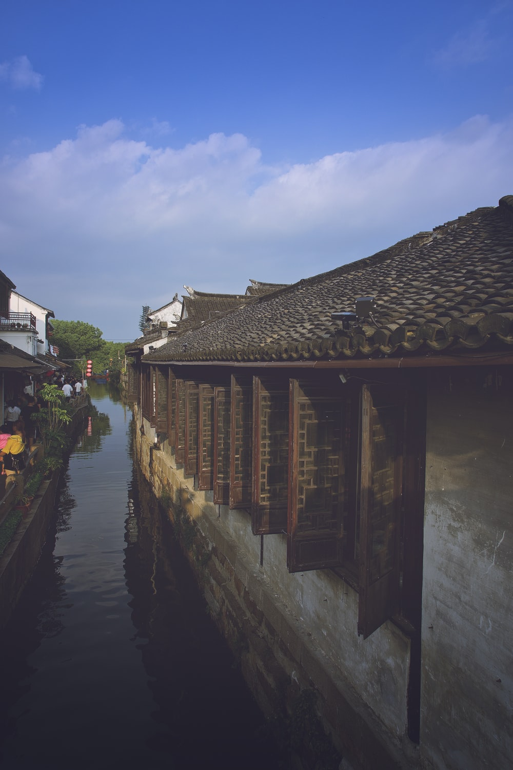 river between houses under white clouds