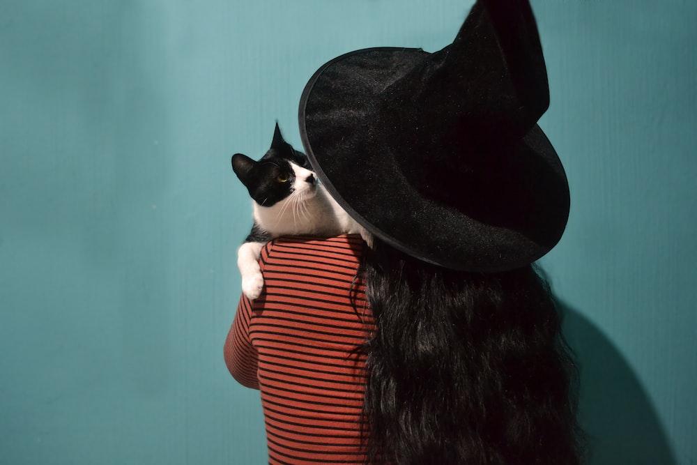 woman carrying tuxedo cat