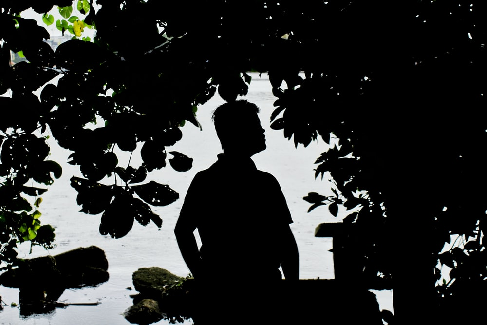 silhouette photography of person beside tree