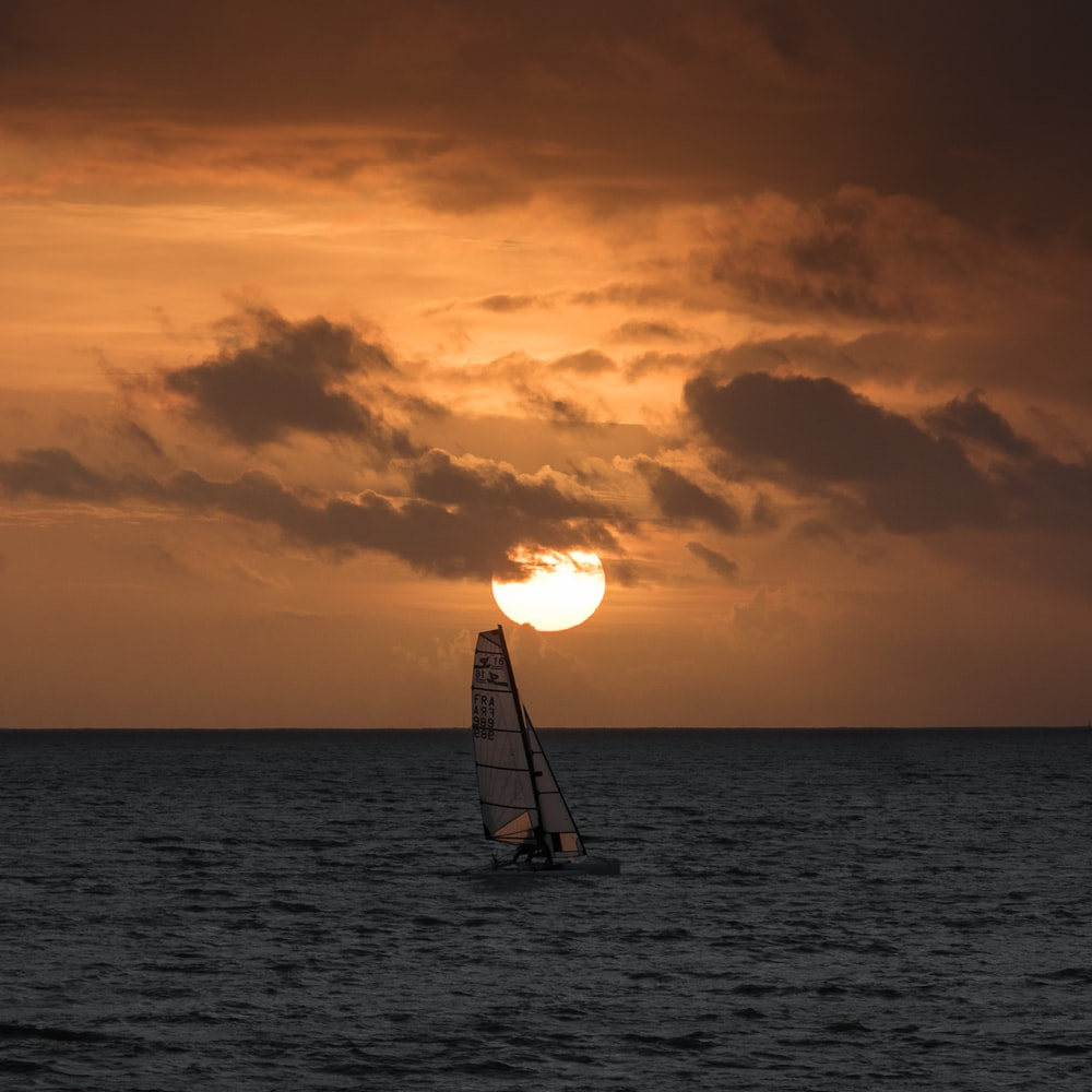 gray sailboat on ocean during daytime