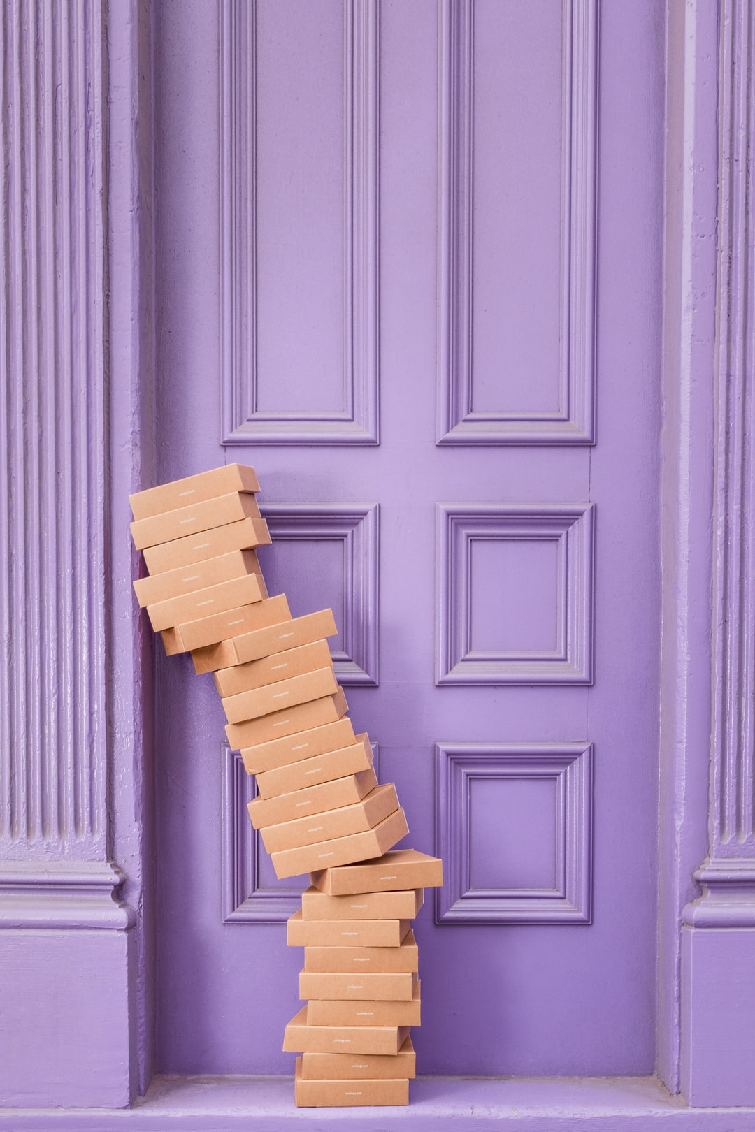 brown boxes stacked in front of a purple door