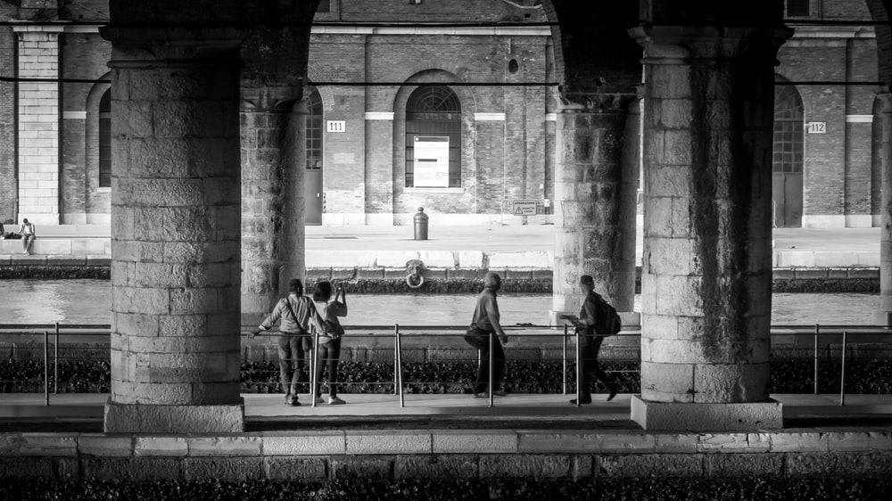 four persons under the bridge in monochrome photo