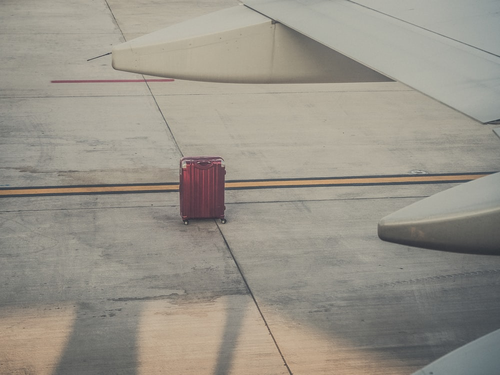 red hard shell luggage by an airplane wing