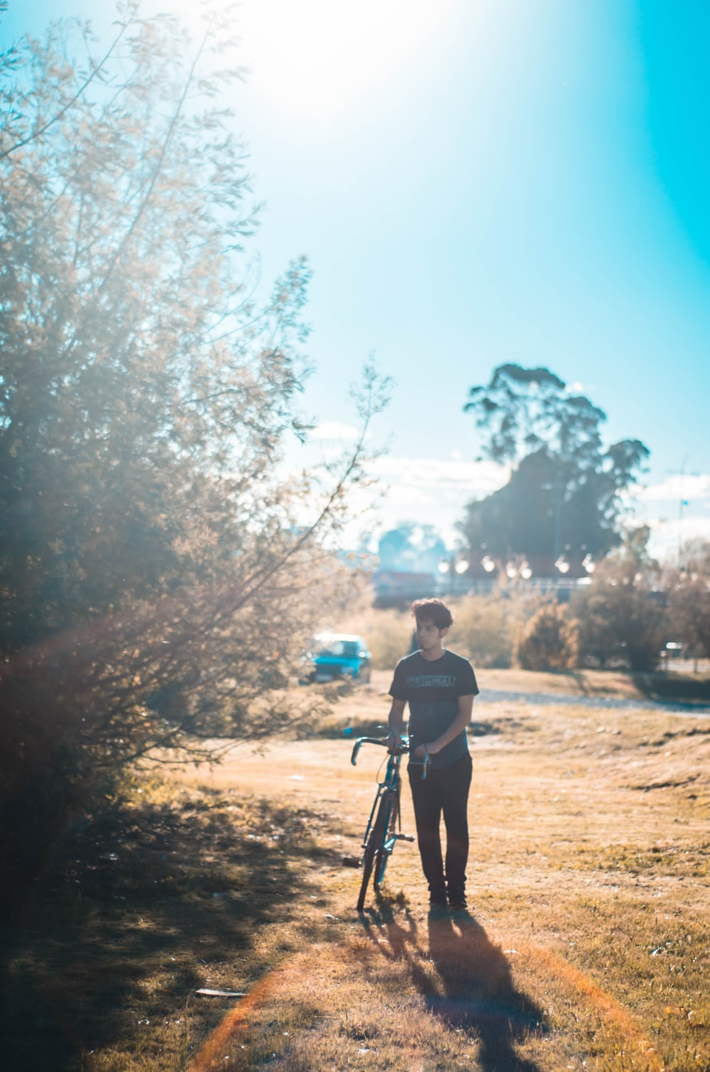 man standing beside bike and tree