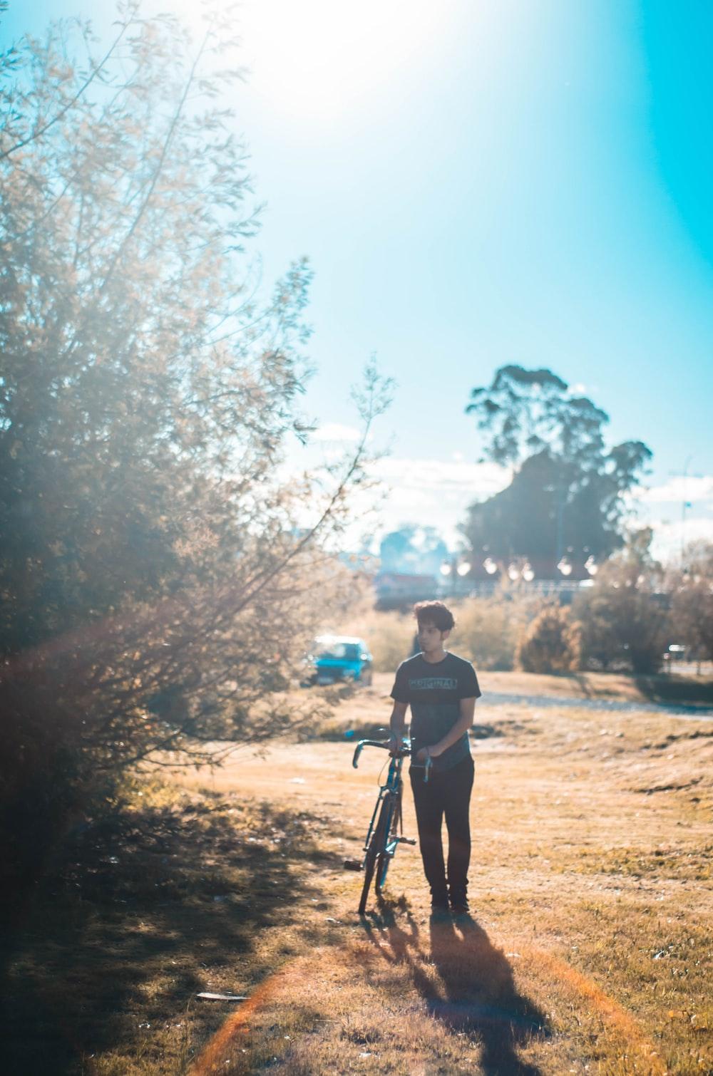 man standing beside bike and tree