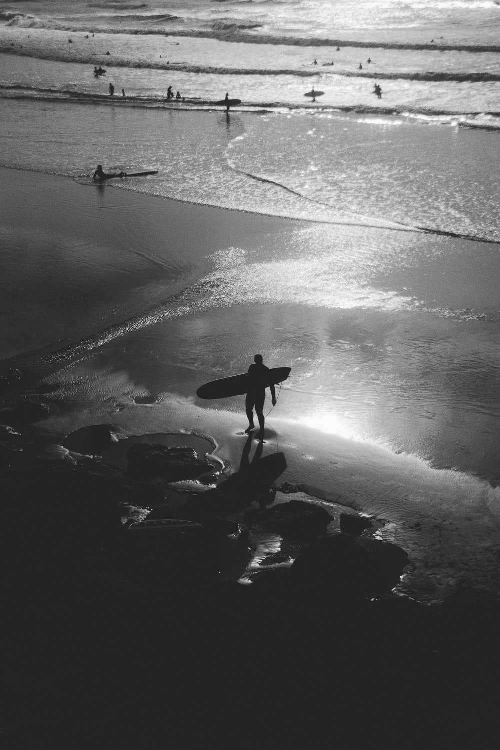 greyscale photography of person carrying surfboard on seashore