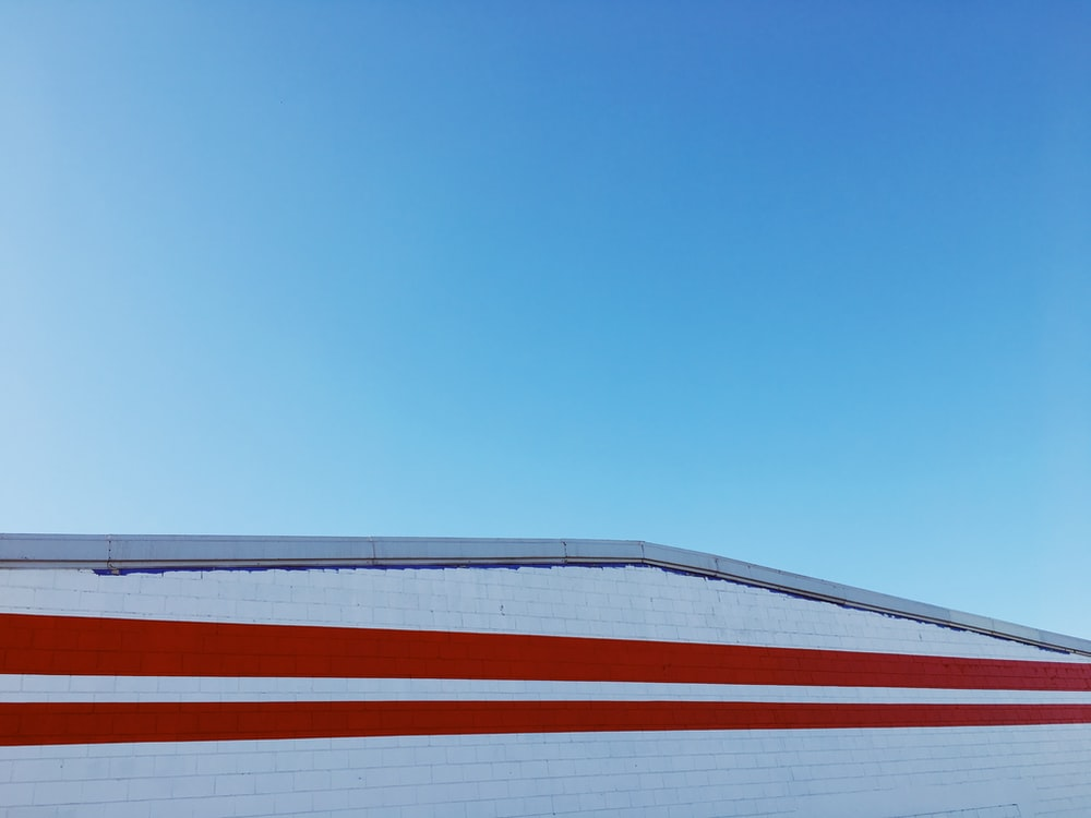 white and red concrete building under blue and white sky during daytime