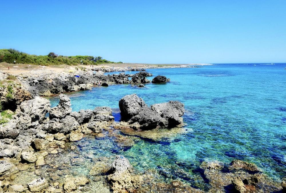 gray stones beside body of water