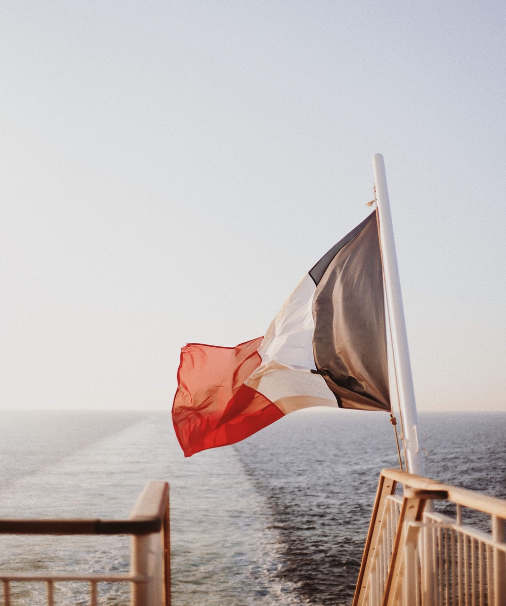 white, red, white, and gray flag waving near sea during daytime