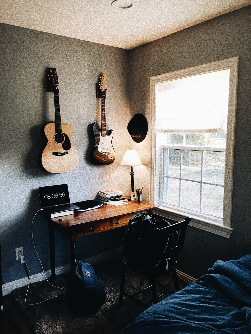 brown acoustic guitar near brown and black electric guitar hanging on wall