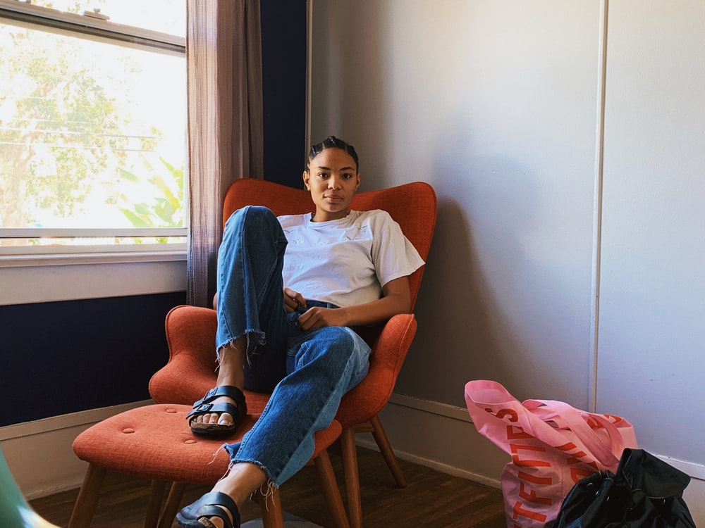 woman sitting on sofa chair beside window