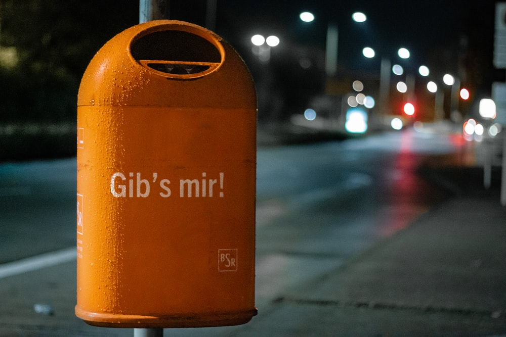orange metal trash bin by roadside at nighttime