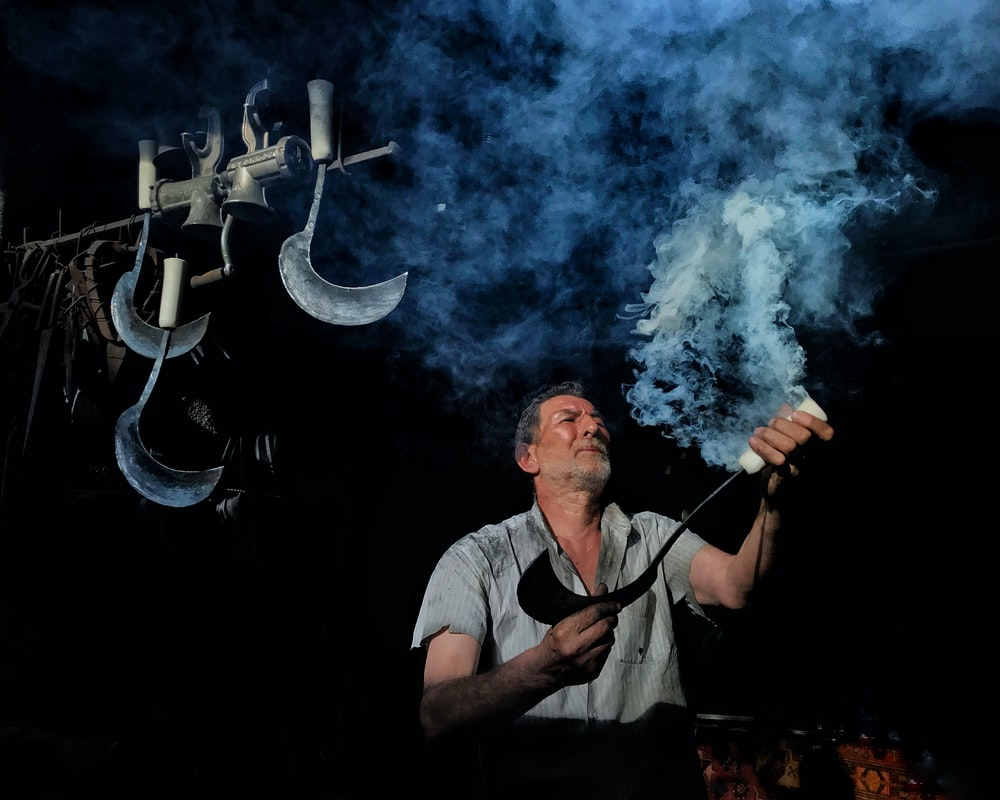 man wearing gray collared button-up shirt holding scythe with white smoke coming out