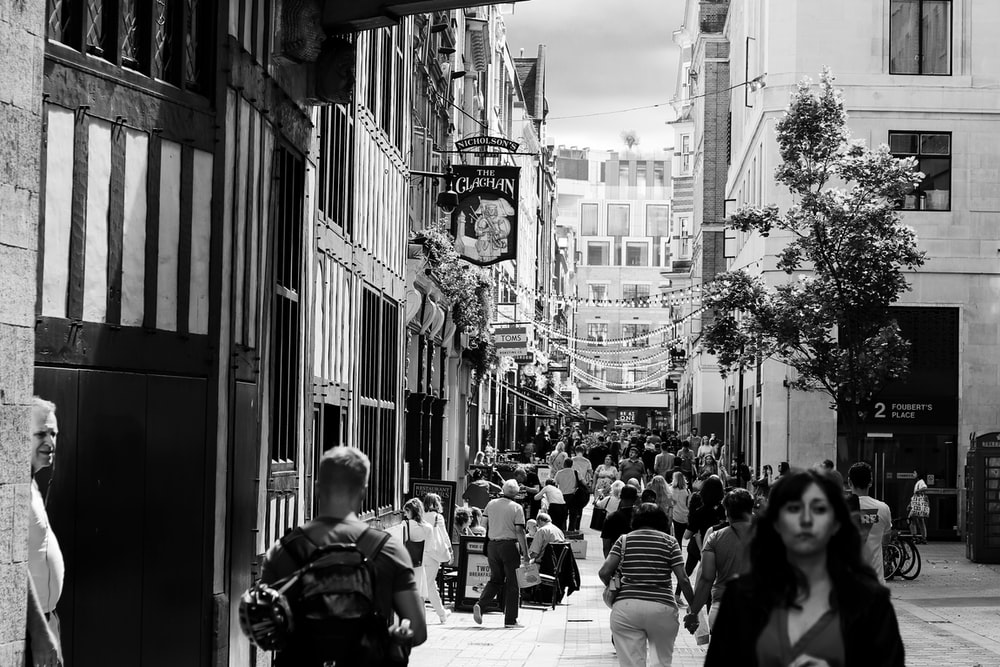 grayscale photo of people at an alley