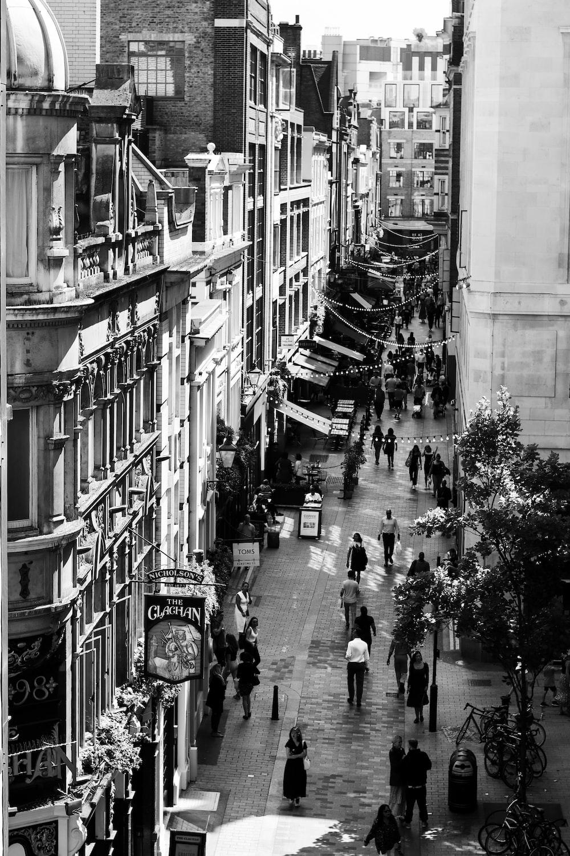 grayscale photography of people walking between buildings
