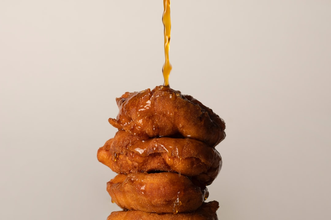 Hot coffee poured over a stack of donuts.