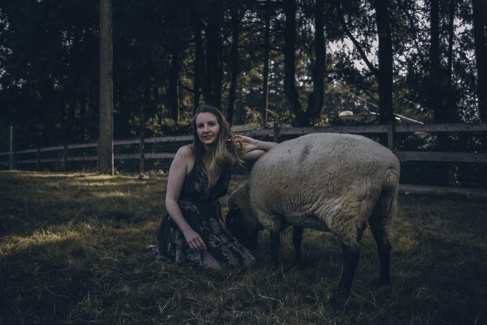 woman beside brown animal